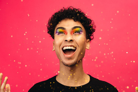 Excited gay man throwing glitter