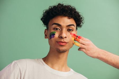 Gay man getting pride flag painted on his face