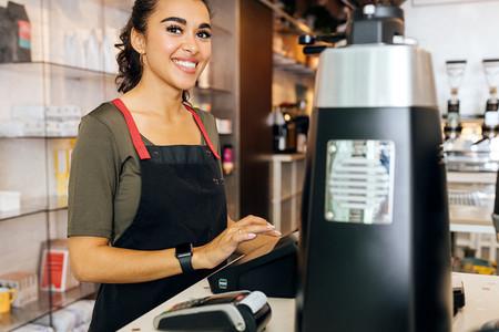 Young beautiful barista standing