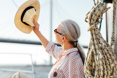 Woman on yacht uses a hat