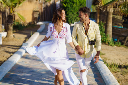 Loving couple walking along a wooden path towards the beach in a coastal area