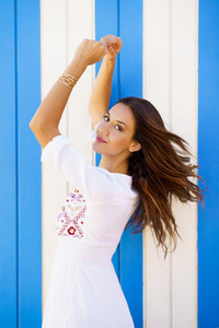 Young woman  fashion model  posing in front of a beach booth