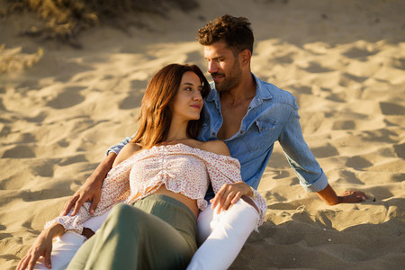 Attractive couple sitting on the sand of the beach enjoying each other