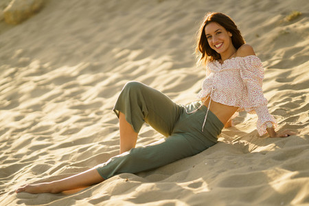 Smiling woman sitting on the sand of the beach