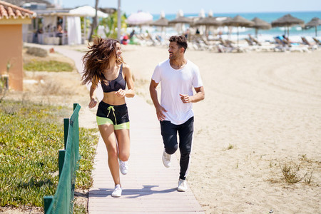 Young couple training running on the beach