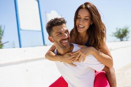 Man carrying his girlfriend piggyback while training near the beach