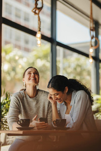 Female friends smiling in a cafe