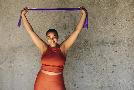 Healthy and fit woman exercising with resistance band