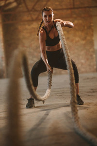 Tough woman working out with battle rope in old warehouse