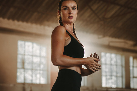 Sportswoman after training session in old warehouse