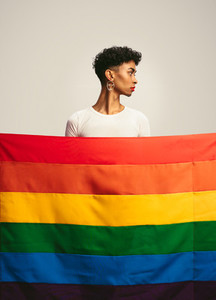 Transgender man behind gay pride flag
