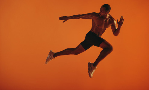 Bare chested male athlete running