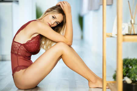 Young adult caucasian woman in red lingerie sitting on the floor