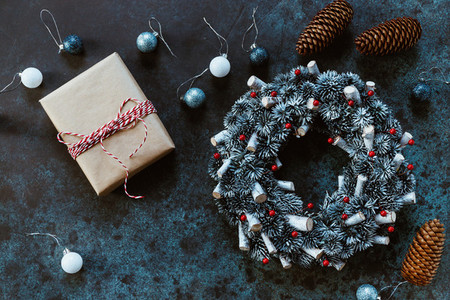 Christmas holiday wreath and a gift box on a blue table among by New Years decor  Top view  flat lay  copy space