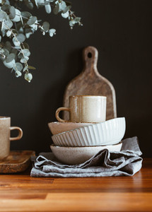 Set of kitchen ceramic tableware and wooden cutting boards on a table Eco style home still life