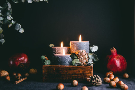New Year festive decorations with wooden box and black burning candles in a dark interior