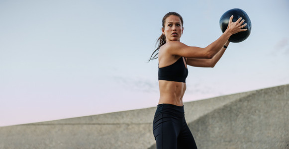 Athletic woman doing fitness training with a medicine ball