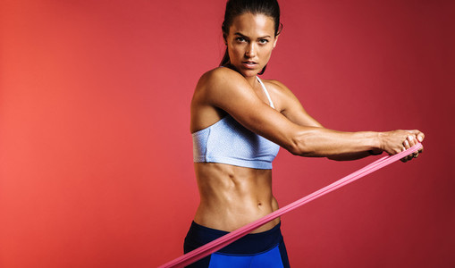 Muscular woman using resistance bands for training