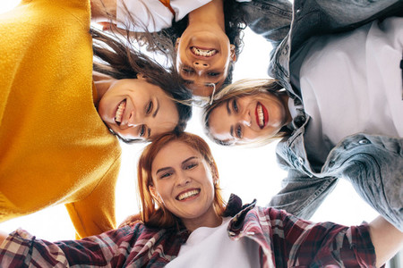 Group of happy female friends huddling outdoors