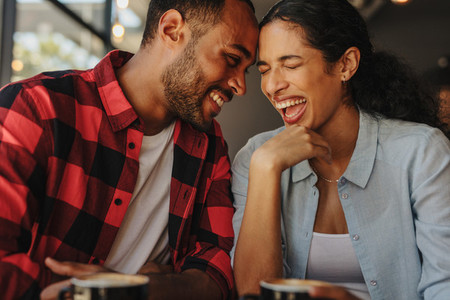 Beautiful couple laughing on a coffee date
