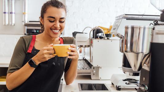 Laughing barista holding a mug