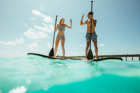 Couple paddleboarding on a tropical beach