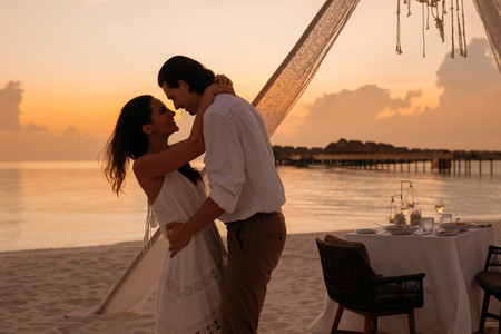 Couple holding each other standing at a beach restaurant
