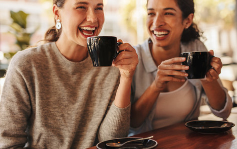 Best friends gossing over coffee