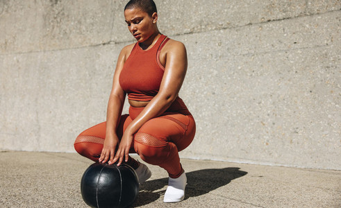 Healthy woman exercising with medicine ball