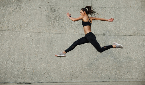 Female athlete running and jumping outdoors
