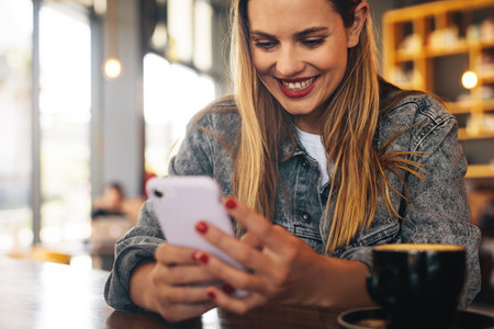 Smiling woman using cafe wifi
