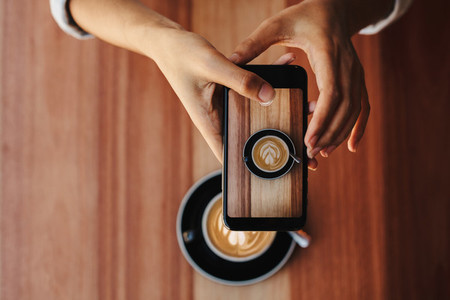 Woman photographing her coffee with phone