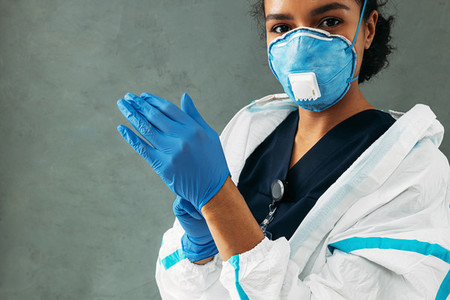 Young medical worker puts on surgical gloves