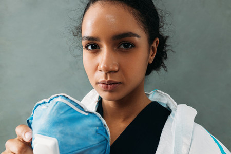 Close up portrait of a tired female nurse holding a respirator