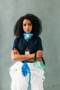 Young serious nurse standing at wall with arms crossed
