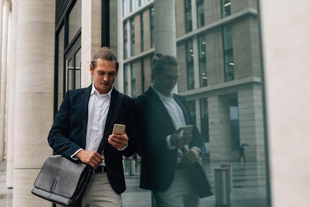 Businessman in formal wear looking on smartphone
