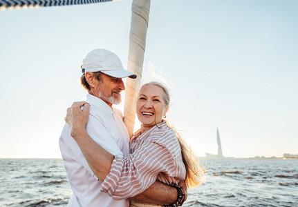Cheerful mature couple embracing outdoors  Happy senior woman looking at camera while standing on yacht