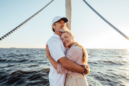 Romantic elderly couple enjoying a sunset on a private yacht