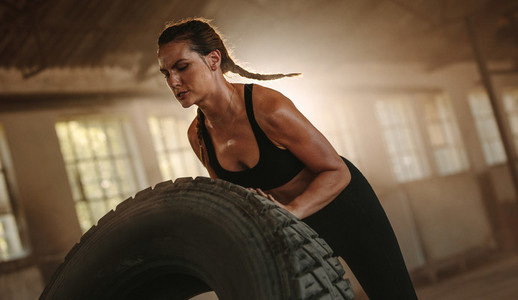 Strong woman doing tire flip workout at old warehouse