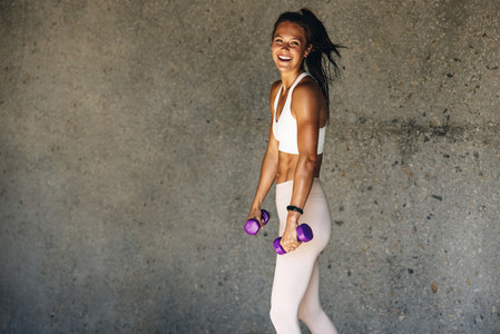Smiling woman with light weight dumbbells