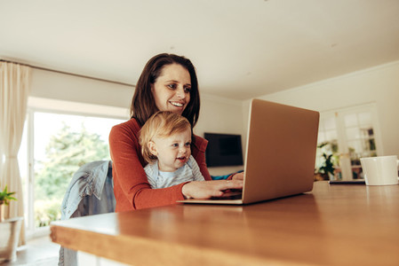 Woman with baby working on laptop