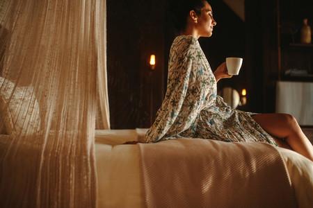 Woman enjoying coffee in bedroom