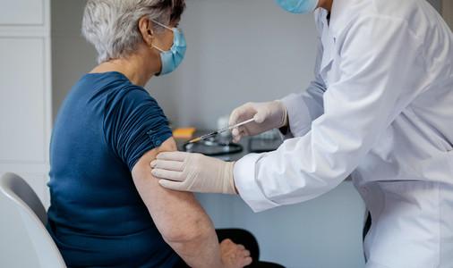 Senior woman being vaccinated against coronavirus