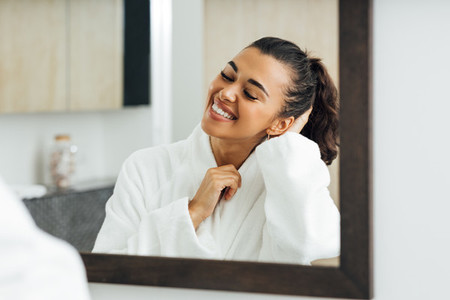 Happy woman in bathroom standing in front of a mirror