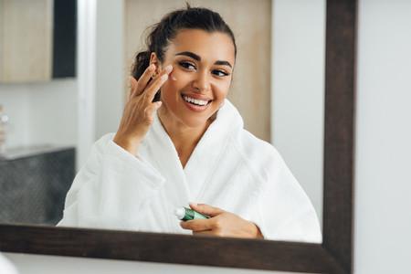 Middle east woman applying cream in bathroom mirror