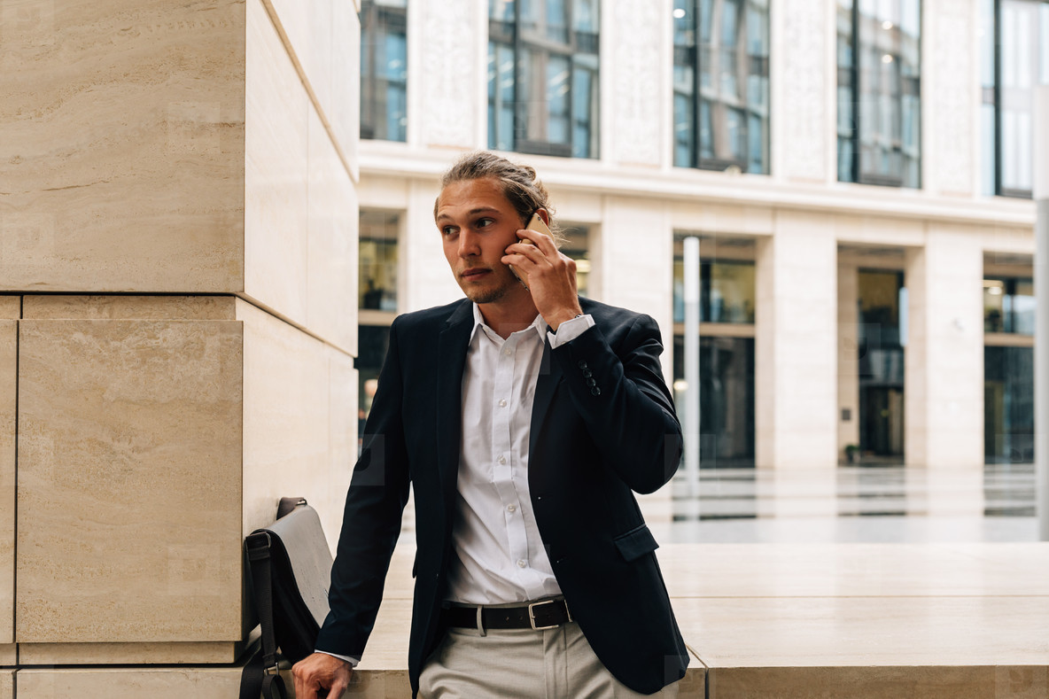 Handsome man in formal wear leaning on a part of office building outdoors