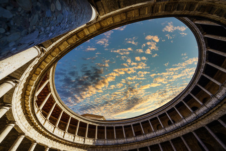 Interior of the Palace of Carlos V in the Alhambra in Granada with a dramatic cloudy sky at sunset