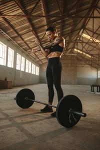 Woman weight lifter doing warm up workout