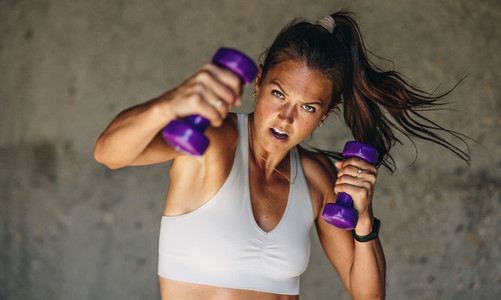 Woman doing shadow boxing with hand weights