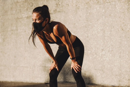 Sporty woman with mask taking rest after workout